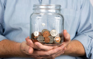 Man holding jar of coins, investing in notes